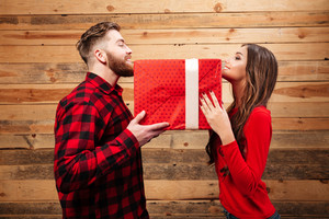 Man and woman holding a gift. so big gift. wooden background