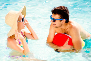 Man and woman in bikini with hat and sunglasses in the swimming pool, with baloon. Summer heat, sun and water.