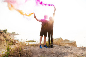 Man and woman in sports wear holding smoke bombs while standing at the rocky beach