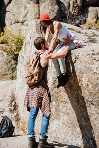 Man and woman teamwork climbing or hiking in summer