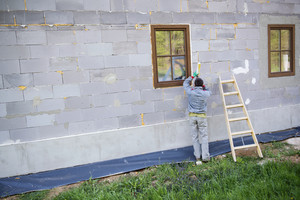 Man applying foam sealant with caulking gun to insulate the window