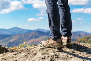 Man at the edge of a cliff high above the mountains