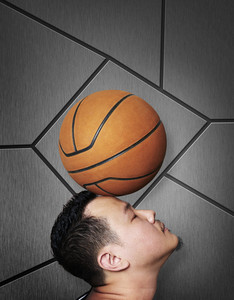 Man balancing basketball on his head ,Orange wall background .