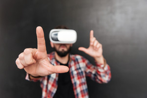 Man dressed in shirt in a cage and wearing virtual reality device standing over chalkboard. Focus on hands.