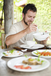 Man enjoying a meal with chopsticks in vietnamese restaurant
