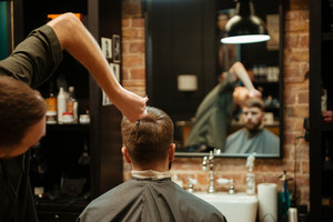 Man getting haircut by hairdresser with scissors while sitting in chair. Look at the mirror. Back view.