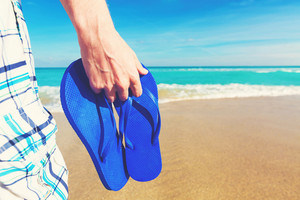 Man holding his sandals at on a tropical beach