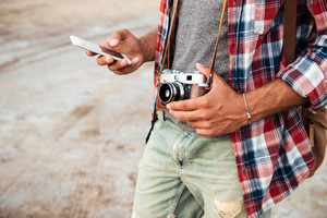 Man holding old vintage photo camera and using mobile phone outdoors