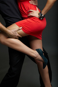 Man holds leg of female in red dress and high-heeled shoes