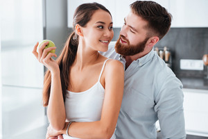 Man hugs woman from behind in kitchen. so good image