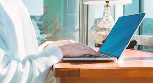Man in a bathrobe on a laptop in bright window lit room