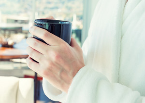 Man in a bathrobe with a cup of coffee in a brightly lit modern interior living space