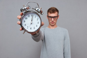 Man in glasses showing clock ant camera. in studio. isolated gray backgroundю Focus on clock