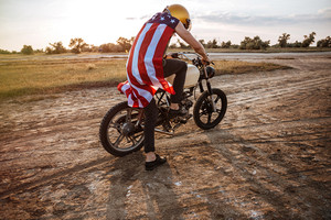 Man in golden helmet and american flag cape starts his motorcycle