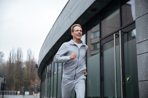 Man in gray sportswear running on the street. From below image