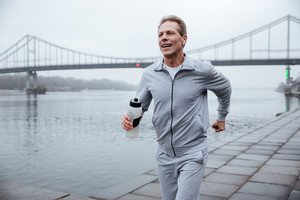 Man in gray sportswear running with bottle of water near the river