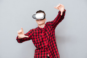 Man in red shirt in virtual reality device showing camera sign. Isolated gray background
