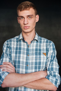 Man in shirt. arms crossed. looking at the camera. isolated black background