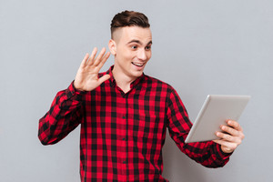 Man in shirt holding tablet computer in one hand waving second hand in tablet. Isolated gray background