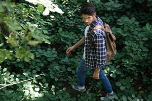 Man in shirt in forest with backpack. from above image.