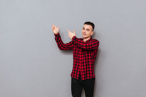 Man in shirt pointing fingers away and looking at camera. Isolated gray background