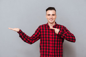 Man in shirt presenting something and pointing on this. Isolated gray background