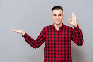 Man in shirt showing ok sign and holding invisible copyspace on the pound. Isolated gray background