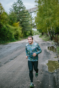 Man in sportswear running on an old road in green nature. Cloudy rainy day.