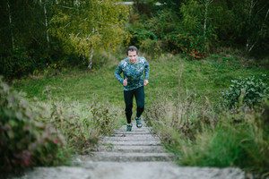 Man in sportswear running up on concrete stairs in green nature. Cloudy rainy day.