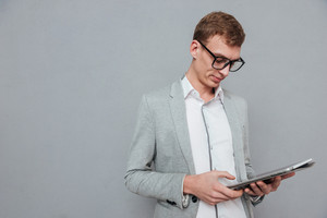 Man in suit and glasses with tablet. looking at tablet. isolated gray background