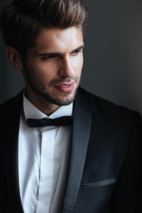 Man in suit. looking away. gray background. close up