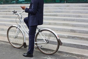 Man in suit writing or reading sms while sitting on bicycle