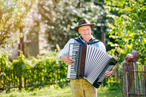 Man in traditional bavarian clothes standing in the garden in front of wooden fence, playing accordion. Oktoberfest.