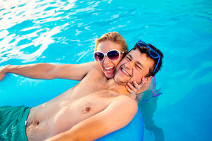 Man in trunks and woman in bikini with sunglasses in the swimming pool. Summer heat and water. Sunny day