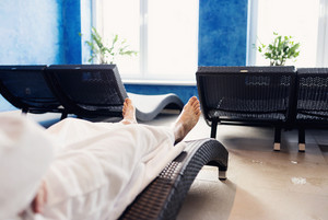 Man in  white bathrobe sitting in lounge chair in spa room