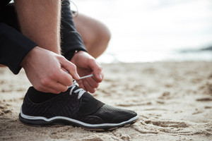 Man is tying shoelace while standing on the sand. Close up