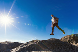 Man jumping over a gap high up on a mountain hike