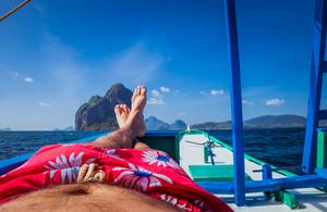 Man laying in banca boat, feet facing Inabuyatan Island by El-Nido, Palawan, Philippines