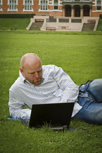 Man laying on the grass working on a laptop in front of school or old office building.