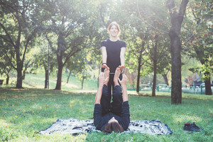 Man lifting up woman with his feet, trai ing outdoor in a park in back light - training, sportive, healthy concept