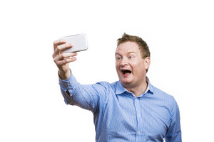 Man making funny faces while taking selfie of himself. Studio shot on white background.
