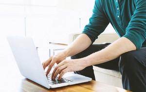 Man on a laptop in bright window lit room