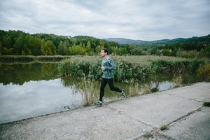 Man on the path at the lake running against green cloudy nature