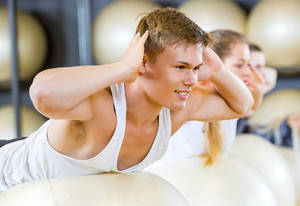 Man Performing Back Extension Exercise With Friends