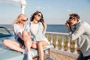 Man photographer taking photos of two gorgeous young women sitting on car in summer