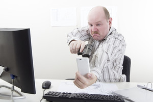 Man points a gun at his mobile / cell phone in his office.