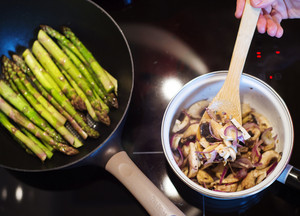 Man preparing creamy mushroom sauce and green asparagus