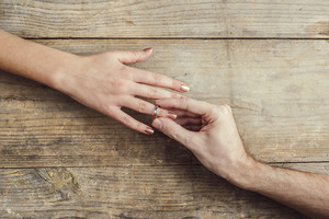 Man putting on engagement ring tenderly to his woman. Studio shot on a wooden background, view from above.