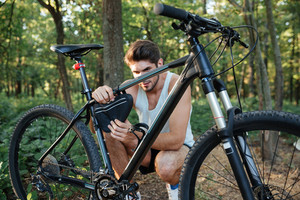 Man repairing a bicycle in forest. side view.