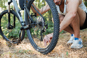 Man repairing mountain bike in the forest. cropped image